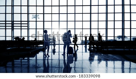 Silhouettes Of Multi-Ethnic Group Of Business People Waiting In Airport Terminal