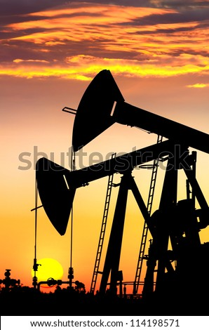 Silhouettes of oil pumps at dawn sky background
