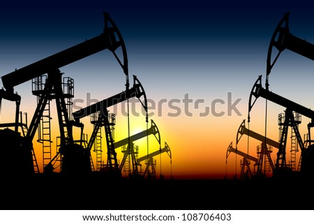 silhouettes of oil pumps placed one after another against the sunset