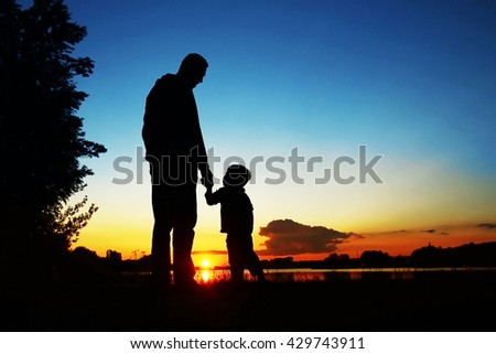 Silhouettes of parents with baby on sunset background