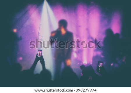 Silhouettes of people and musicians in big concert stage. Bright beautiful rays of light #398279974