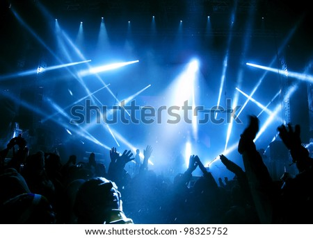 Silhouettes of people and musicians in big concert stage. Bright beautiful rays of light