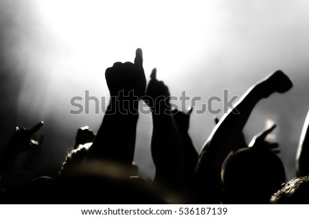 silhouettes of people at a concert in front of the scene in bright light #536187139