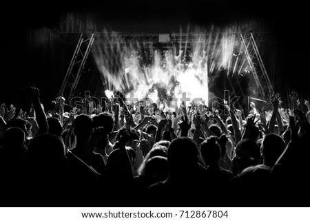 Silhouettes of people at a concert in front of the scene in bright light. Black and White #712867804