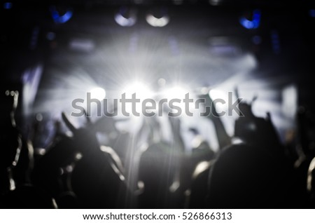 silhouettes of people at a concert in front of the scene in orange bright light. Hands with gesture Horns. That rocks