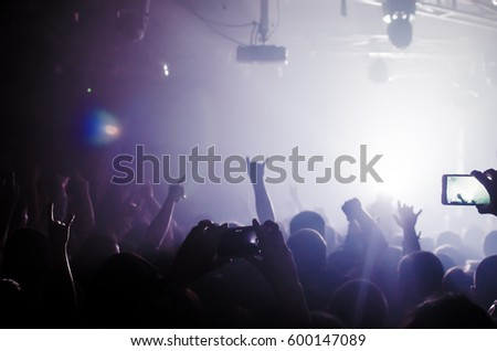silhouettes of people at a rock festival concert in front of the scene in bright light #600147089