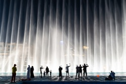 Silhouettes of people enjoying the fountain show in Dubai at night, United Arab Emirates