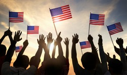 Silhouettes of People Holding the Flag of USA