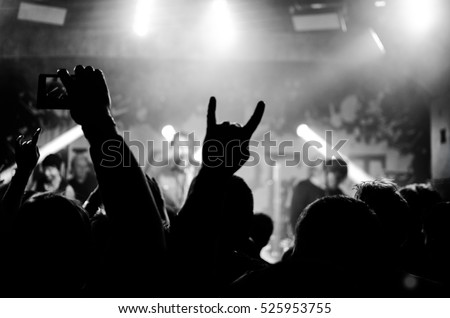 Silhouettes of people in a bright in the pop rock concert in front of the stage. Hands with gesture Horns. That rocks. Party in a club  #525953755