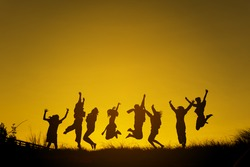 Silhouettes of People jumping in sunset.