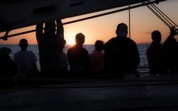 Silhouettes of people standing together on a boat with a stunning sunset.
