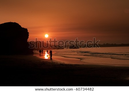 Silhouettes of people walking by a beach at sunset.