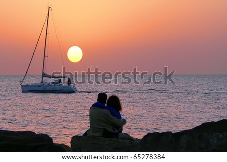 Silhouettes of people, yacht and orange sunset of the sea