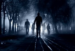 Silhouettes of people zombie walk at night in the city in the moonlight in the soft blurred focus on a dark blue background. Artistic image of a zombie people.