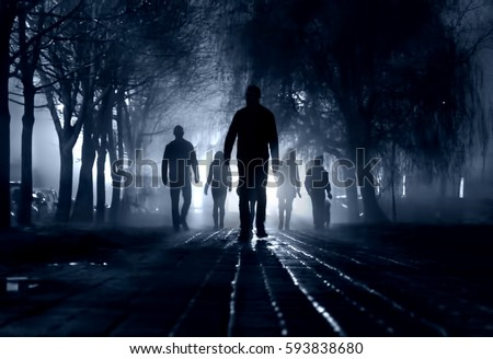 Silhouettes of people zombie walk at night in the city in the moonlight in the soft blurred focus on a dark blue background. Artistic image of a zombie people