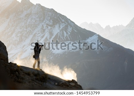 Silhouettes of photographer while taking photograph from top of a mountain, Silhouette tourists and photographers with beautiful sunrise and mist
