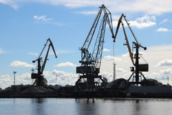 Silhouettes of port cranes against a blue sky