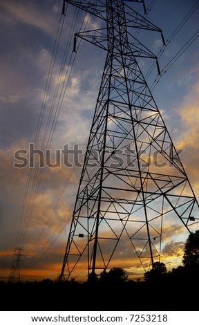 Silhouettes of power lines and towers with a brilliant sunset - stock photo