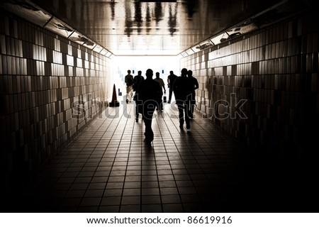 Silhouettes of random unrecognizable people walking in a tunnel.