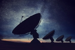 Silhouettes of satellite dishes or radio antennas against night sky. Space observatory.