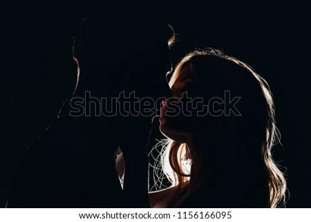 silhouettes of sensual heterosexual couple kissing in dark #1156166095