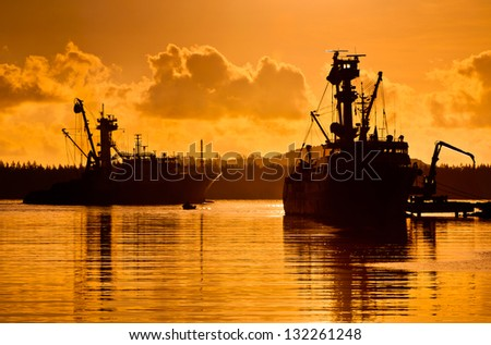 Silhouettes of ships arriving in the harbor at sunset