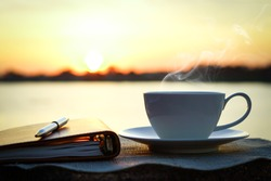 Silhouettes of sunrise morning coffee with a note and a pen