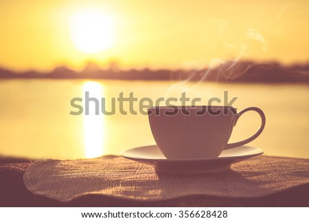 Stock Photo Silhouettes of sunrise morning coffee with a note and a pen
