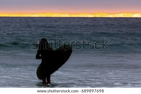Silhouettes of surfers standing at the shoreline looking out to sea with their surfboard in their hands getting ready to enter the ocean waves