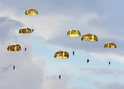 Silhouettes of the army skydiver team against dramatic sky.