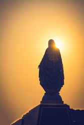 Silhouettes of the blessed Virgin Mary statue figure in a warm tone - sunset scene. Catholic praying for our lady - The Virgin Mary.