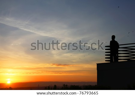 Silhouettes of the boy standing on a balcony and looking at flying birds on the sunrise background