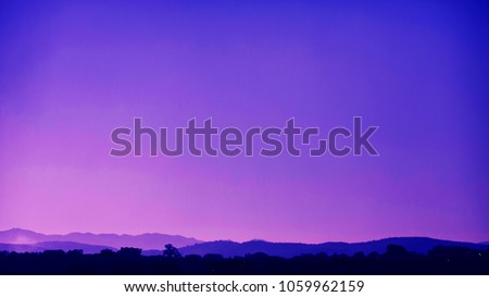 Silhouettes of the mountain hills at purple sunset. Mountain cascade background