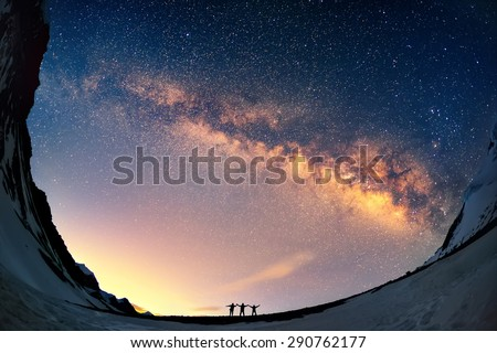 Silhouettes of the people standing together holding hands against the Milky Way in the mountains.