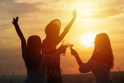 Silhouettes of three happy young girls with hands up sitting and drinking wine on beautiful sunset.