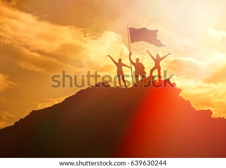 Silhouettes of three people holding a national flag of victory on a man on top of a mountain, hands up. Conceptual design. Against the dramatic sky with clouds at sunset. Business success.