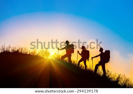 Silhouettes of three people walking with backpacks and other hiking gear up toward top of wild grass mountain mother father daughter bright luminous sunrise sky background