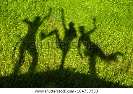 silhouettes of three persons standing with their hands stretched up
