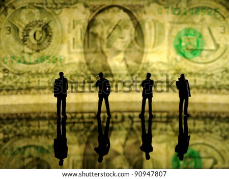 silhouettes of tiny businessman figures against one dollar bill
