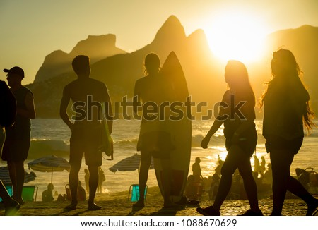 Silhouettes of tourists and surfers gather to watch the sunset at Arpoador, a popular summertime activity for locals and travelers. #1088670629