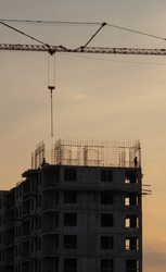 Silhouettes of tower cranes against the evening sky. House under construction. Industrial skyline