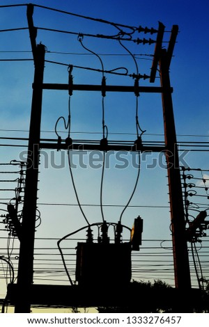 Silhouettes of transformers on the pole Three-phase transformer for AC power conversion is a high voltage cable, low voltage and low voltage, cable below On a cool turquoise background #1333276457