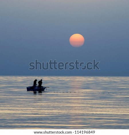 silhouettes of two fishermen fishing in boat on sea at gorgeous sunrise in Tunisia
