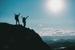 Silhouettes of two happy hikers in winner poses with raised arms are standing on mountain top