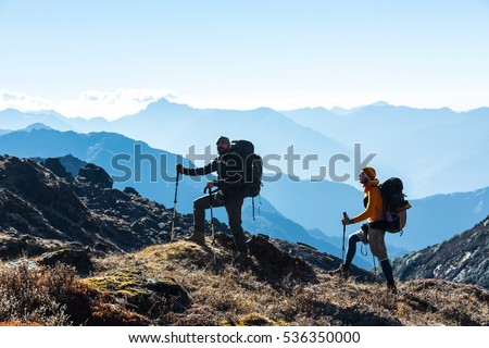Shutterstock Silhouettes of two Hikers staying on rocky and grassy Ridge with Backpacks and other Gear expressing Energy and Happiness. Layered Mountain Valley View on Background