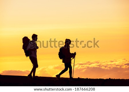 Silhouettes of two hikers with backpacks walking at sunset. Trekking and enjoying the sunset view from mountain top above the clouds.