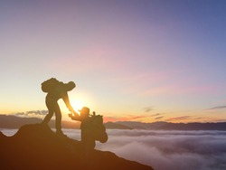 Silhouettes of two people climbing on mountain and helping. assistance and hiking and team work concept.