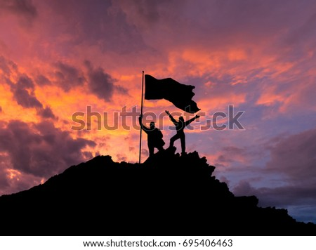 Silhouettes of two people on top of a mountain. Man and woman. Couple in love. Raising his hands, with the flag of victory. Against the background of the evening sky with clouds at sunset.
