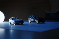 Silhouettes of two scale models of a sedan car and a SUV 4×4 all terrain vehicle, in the dark with blue shades, white light, shadows and clair-obscur effects