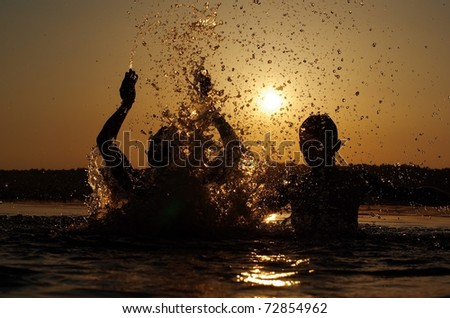Silhouettes of two young men playing in the lake on sunset - stock photo